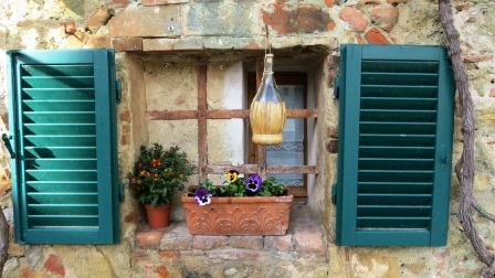 Un finestra con un tipico fiaschetto di vino  in un piccolo borgo della toscana